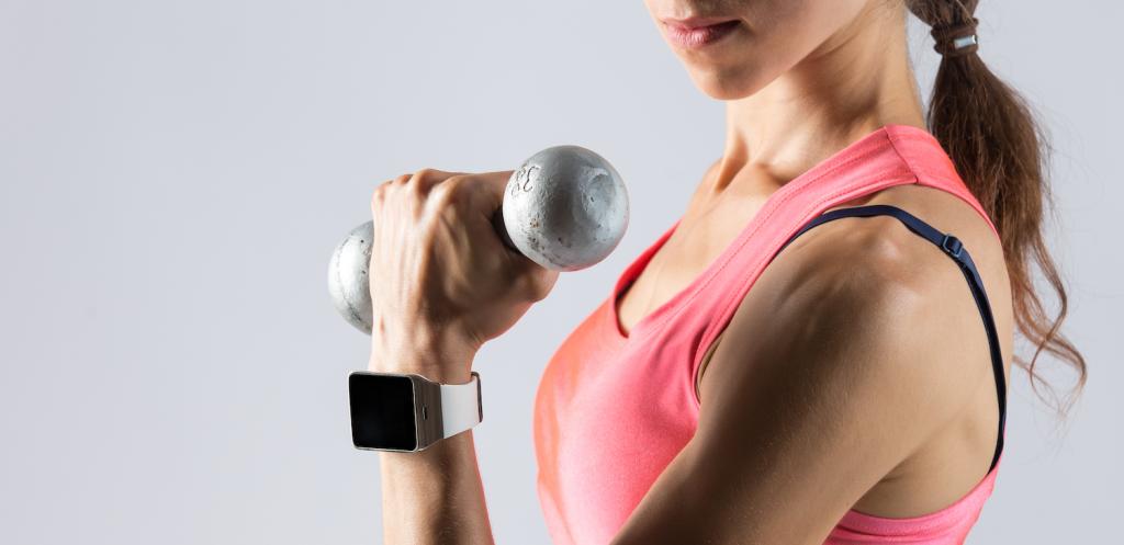 Mujer levantando pesas con reloj deprotivo